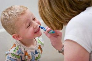 toddler-getting-teeth-brushed
